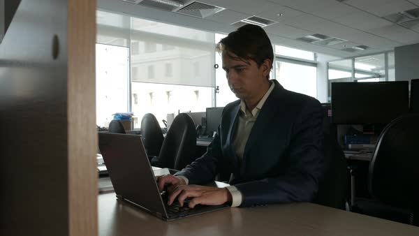 Young Businessman Working On His Laptop At His Desk Dolly Slider Shot Stock Footage
