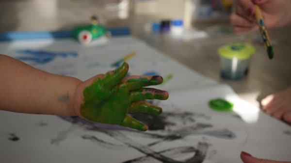 Woman paints a child's hand with green