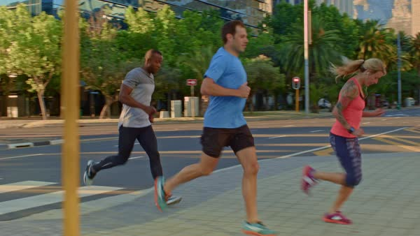 Group of people running across the crossing, completing their run exercise  together accomplish fitness goal stock footage