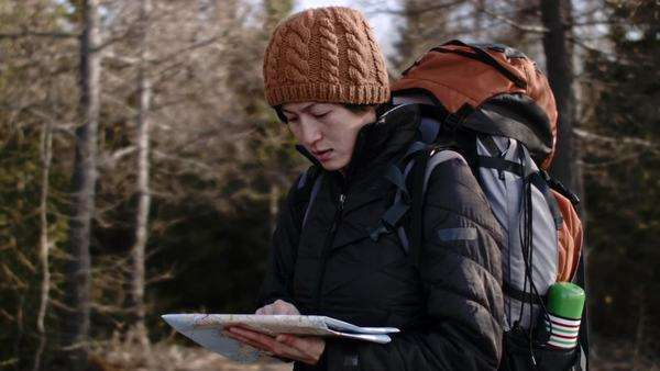 Outdoors woman with hiking backpack holding map looking for directions Royalty-free stock video
