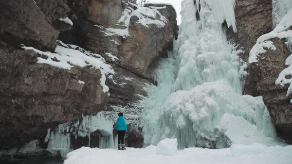 Wide-angle shot of a woman looking at a frozen waterfall in Johnston Canyon Royalty-free stock video