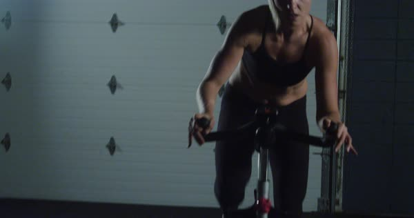 Medium shot of a woman riding a spin bike Royalty-free stock video