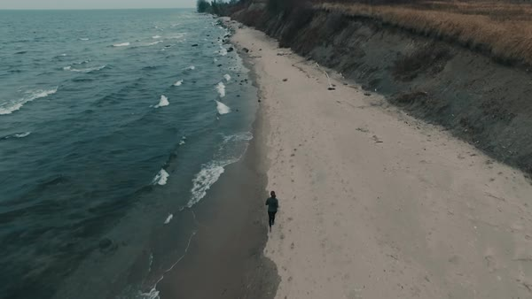 Aerial of woman running along beach in fall Royalty-free stock video