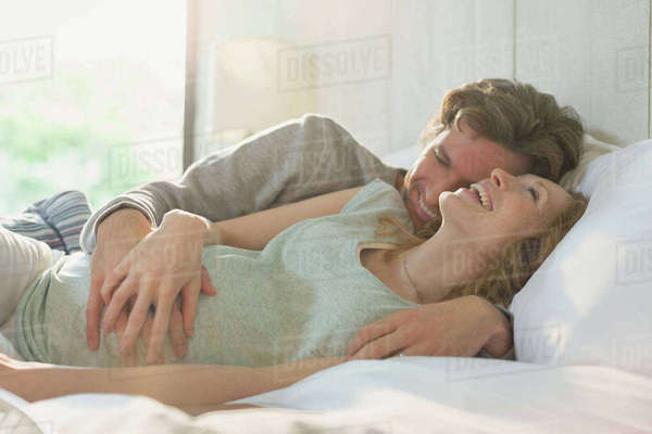 affectionate pregnant couple laying in bed laughing stock photo dissolve. Black Bedroom Furniture Sets. Home Design Ideas