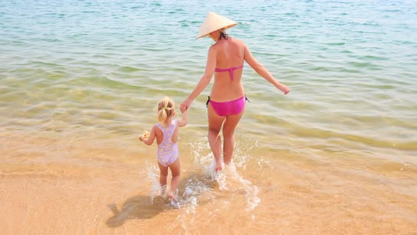 21e8474162 Backside blond mother in hat and pink bikini brings little daughter across  wet sand beach to azure sea - Stock Video Footage - Dissolve