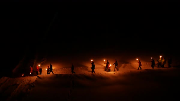 Aerial shot of people walking in snow with burning torches Royalty-free stock video