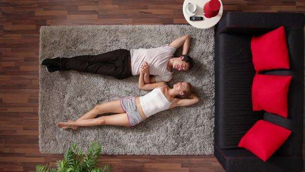 Medium shot, Lockdown, couple lying on a rug talking and holding hands, overhead view Royalty-free stock video