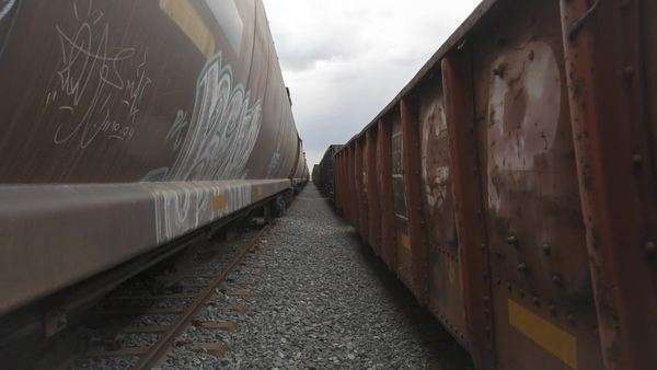 Slider shot between two train cars full of graffiti Royalty-free stock video