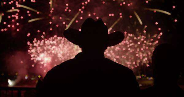 Fireworks explode in the distance between silhouettes of people Royalty-free stock video