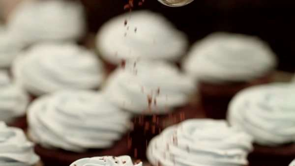 Freshly baked cupcakes topped off with chocolate shavings from a measuring spoon Royalty-free stock video