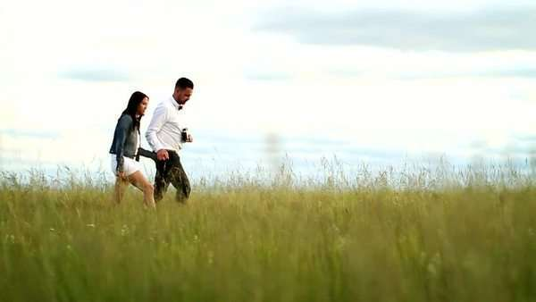 Couple walking through field when female starts running ahead to pose for a photo Royalty-free stock video