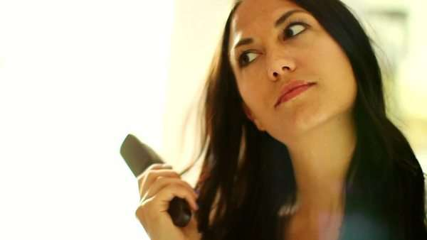 Young woman brushes her hair and looks in the mirror Royalty-free stock video