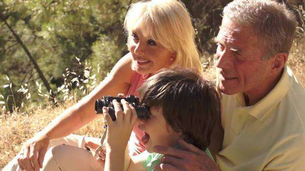 Senior couple and grandchild sitting in countryside enjoying views with binoculars. Royalty-free stock video