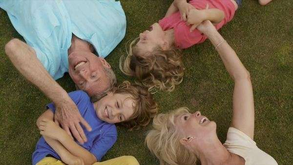 Overhead shot of grandparents and grandchildren lying on grass in garden. Royalty-free stock video