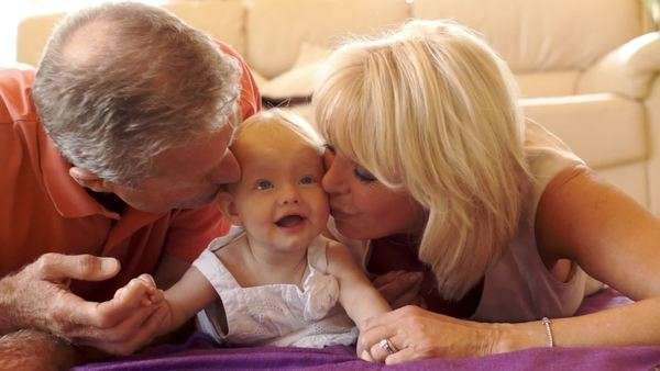 Grandparents and baby granddaughter lying on floor looking at camera. Royalty-free stock video