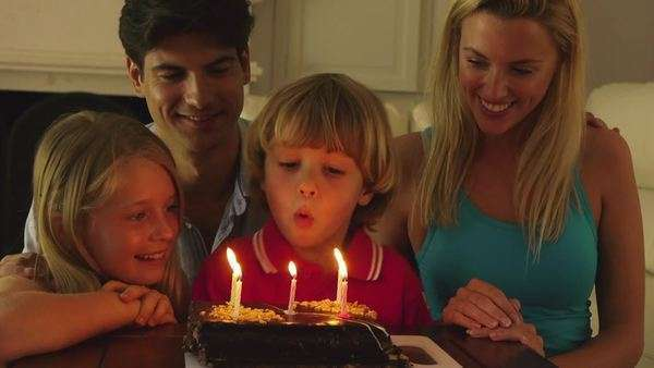 Boy blowing out candles on birthday cake. Royalty-free stock video