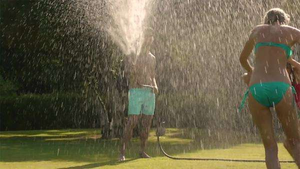 Family playing in sprinkler in garden. Royalty-free stock video