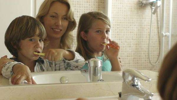 Children brushing their teeth with mother. Royalty-free stock video
