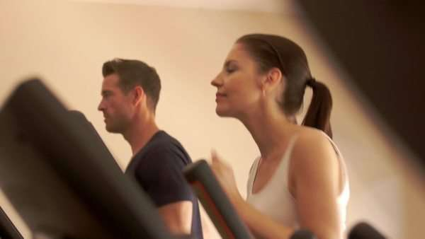 Lift up shot of couple exercising on treadmill at gym. Royalty-free stock video
