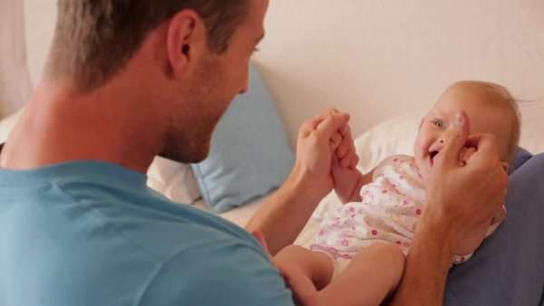 Rear view of father playing with baby daughter on bed. Royalty-free stock video
