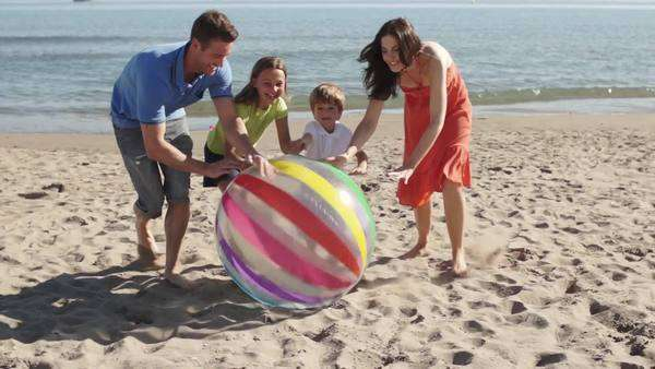 Slow motion shot of family on beach rolling beach ball towards camera. Royalty-free stock video