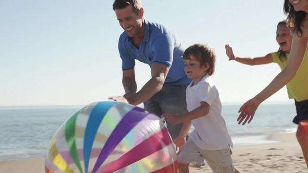 Slow motion shot of family chasing beach ball along beach Royalty-free stock video