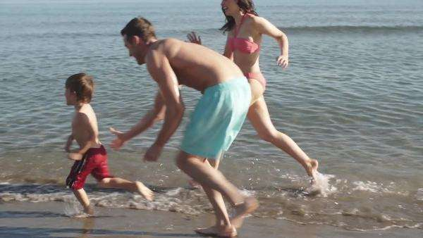 Family running along beach at edge of sea. Royalty-free stock video