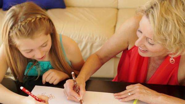 Dolly shot of grandmother and granddaughter drawing together indoors. Royalty-free stock video