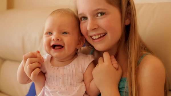 Girl and her baby sister together on sofa Royalty-free stock video