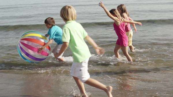 Slow motion of five children playing in surf with beach ball. Royalty-free stock video