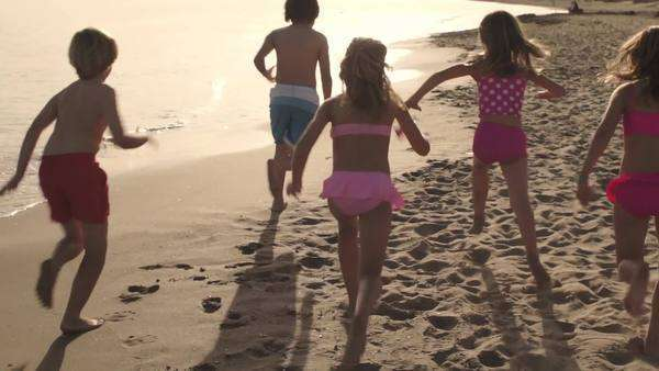 Slow motion of five children running away from camera on beach. Royalty-free stock video