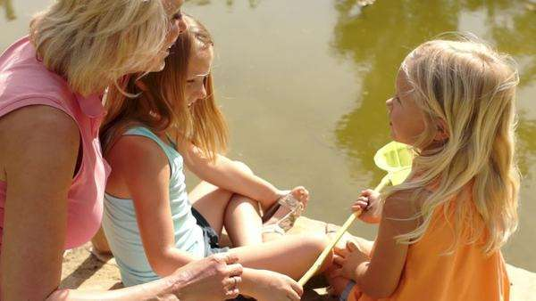 Grandmother and two granddaughters fishing with net in pond in park. Royalty-free stock video