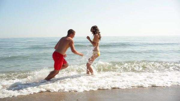 Young couple splashing on beach Royalty-free stock video