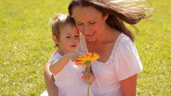 mother and baby playing with flower in park Royalty-free stock video
