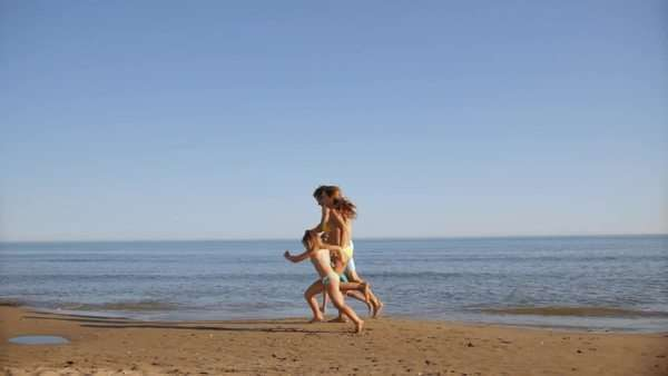 pan shot of family running on beach Royalty-free stock video