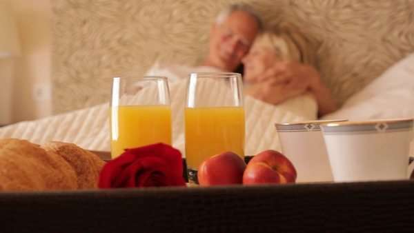 dolly shot of senior couple sitting in bed with breakfast in foreground Royalty-free stock video