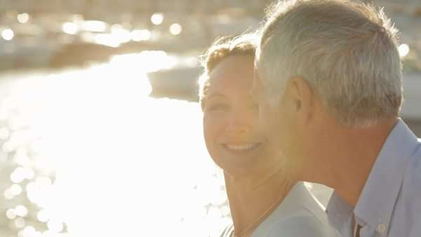 head and shoulders shot of senior couple sitting together by marina in sunset Royalty-free stock video