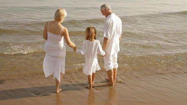 grandparents and granddaughter standing on beach Royalty-free stock video