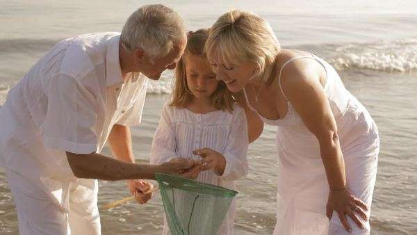 grandparents and granddaughter on beach with fishing net Royalty-free stock video