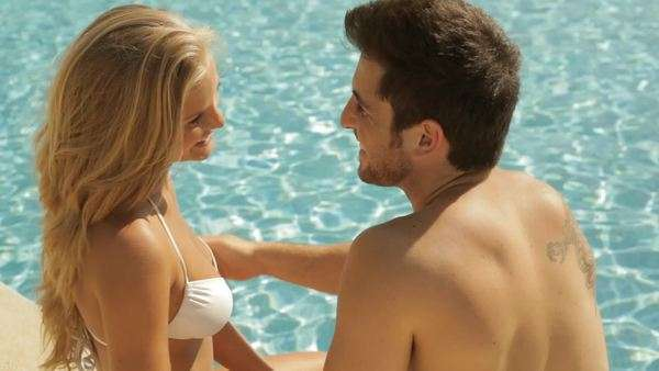 young couple sitting by side of pool Royalty-free stock video