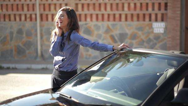 Woman leaning on car while talking on cell phone. Royalty-free stock video