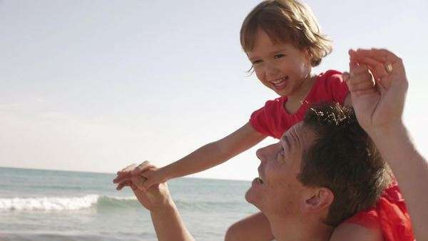 Father giving his daughter a shoulder ride at beach. Royalty-free stock video