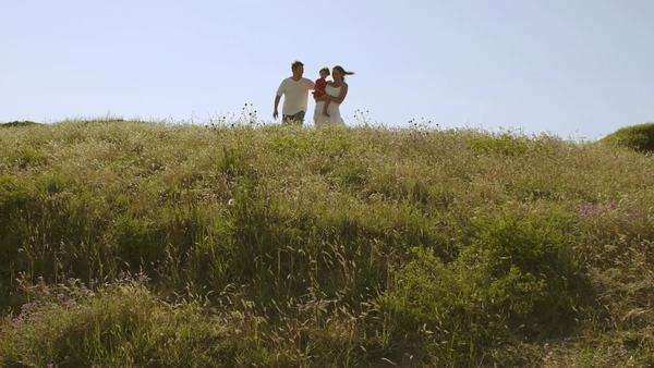 Family walking through meadow to camera. Royalty-free stock video