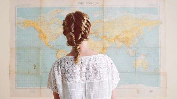 Tourist girls looking at world map planning travel adventure stock tourist woman looking at world map planning travel adventure royalty free stock video gumiabroncs Image collections