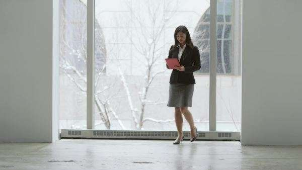 Young asian business woman walks away from window and towards the camera, becoming a silhouette Royalty-free stock video