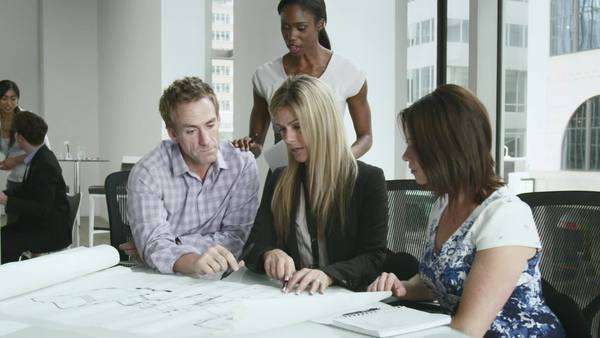 An african-american woman approaches three colleagues sitting at a table going over blueprints Royalty-free stock video