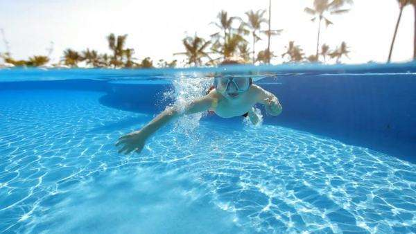 Young boy swimming in pool at tropical resort Royalty-free stock video