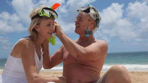 Senior couple helping each other with snorkel gear Royalty-free stock video