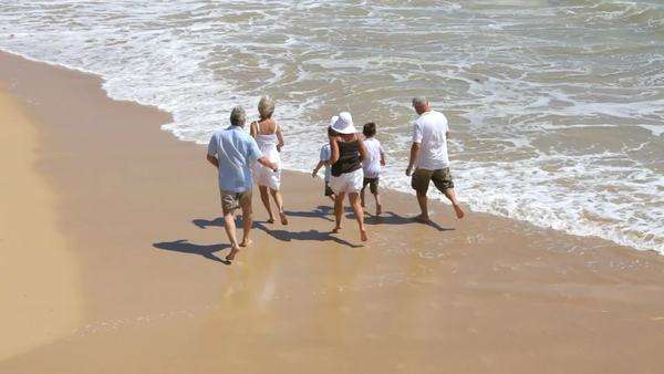 Multi-generation family running on beach together Royalty-free stock video