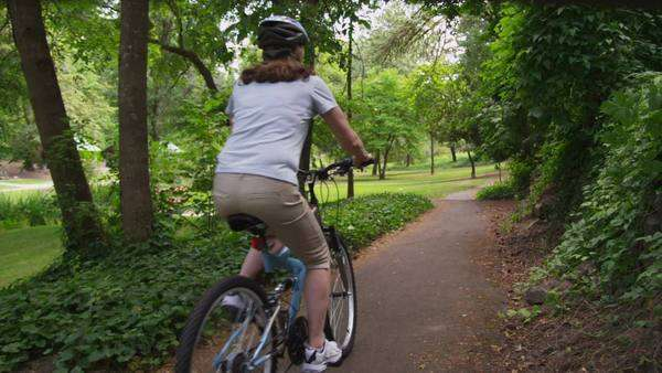 Mature couple riding bicycles through park Royalty-free stock video